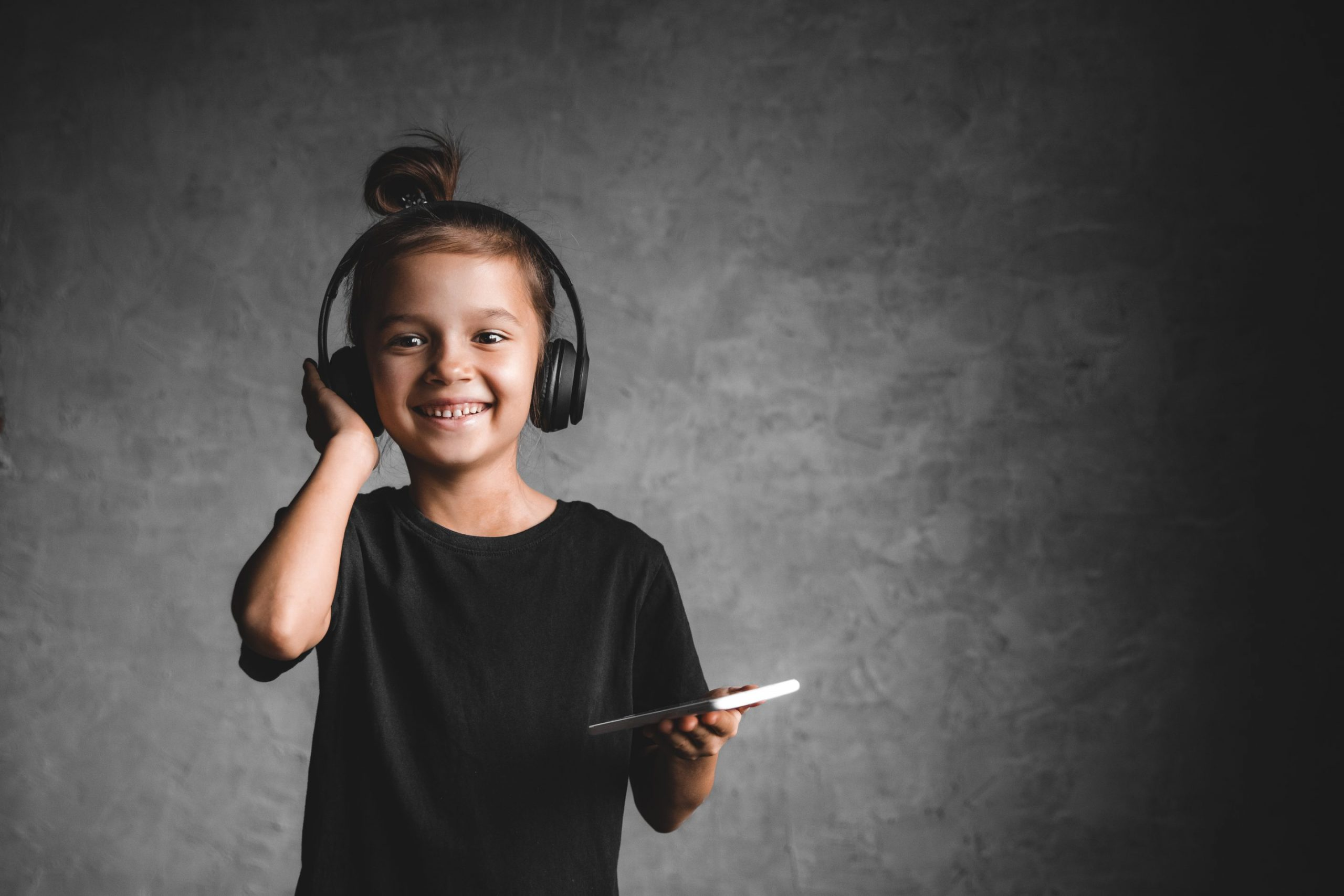 Kiedel little girl with headphones and phone on a gray ba 4LZDYTC scaled 1 scaled