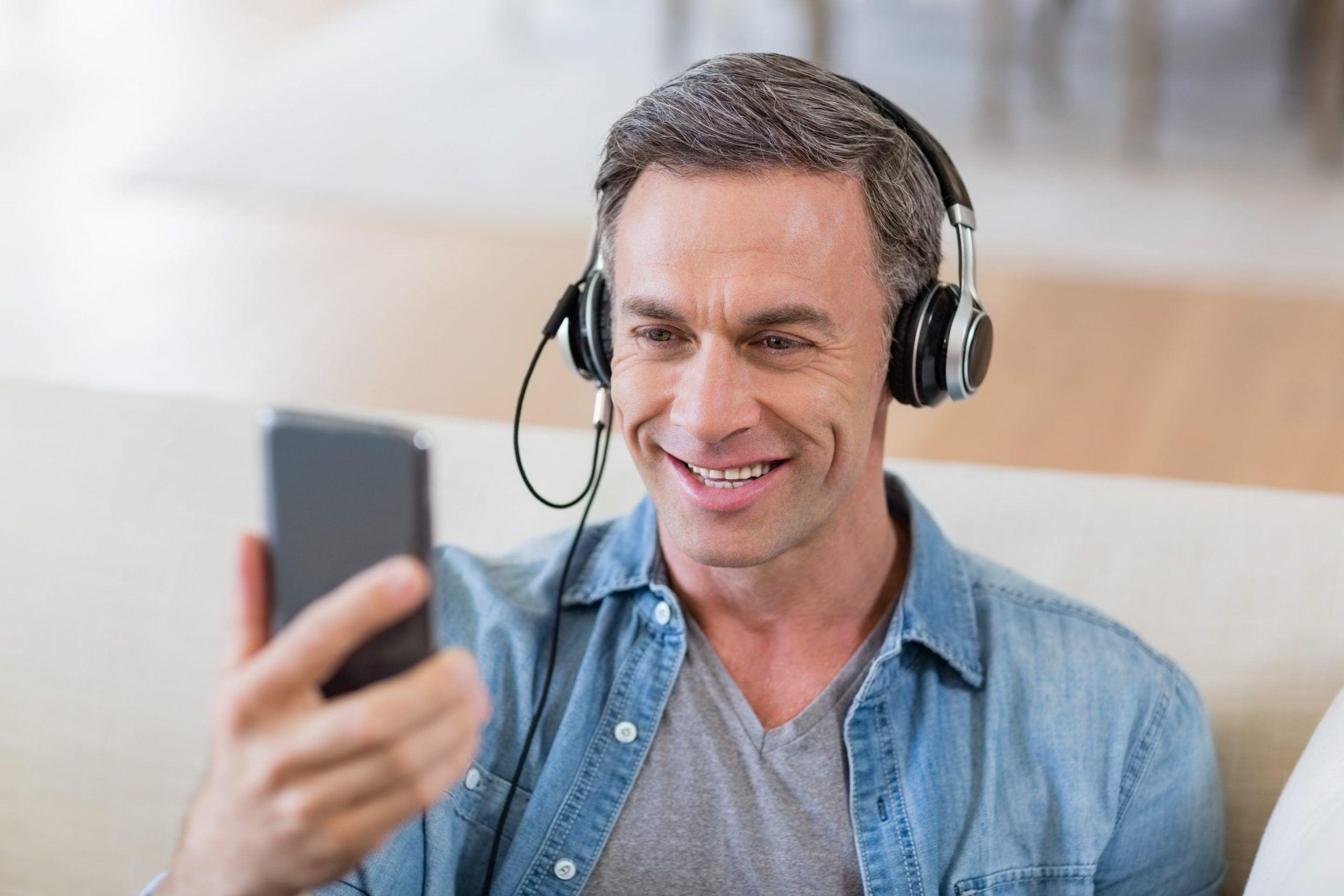 Kiedel man listening to music on headphones in living roo VFMS2RS scaled 1 scaled